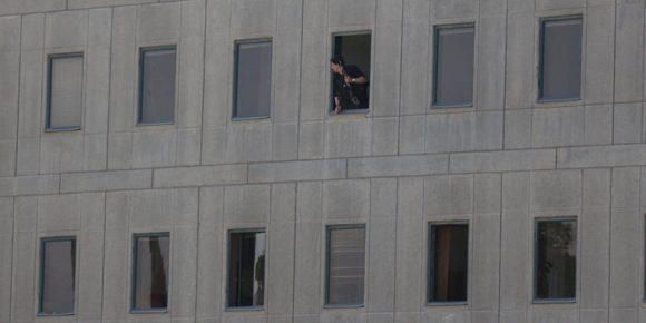 Un poliziotto affacciato a una finestra del parlamento iraniano (TIMA via REUTERS)